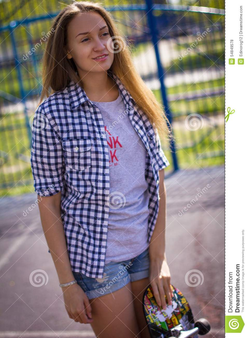Cute Girl In Shorts With A Skateboard On The Playground Stock ...