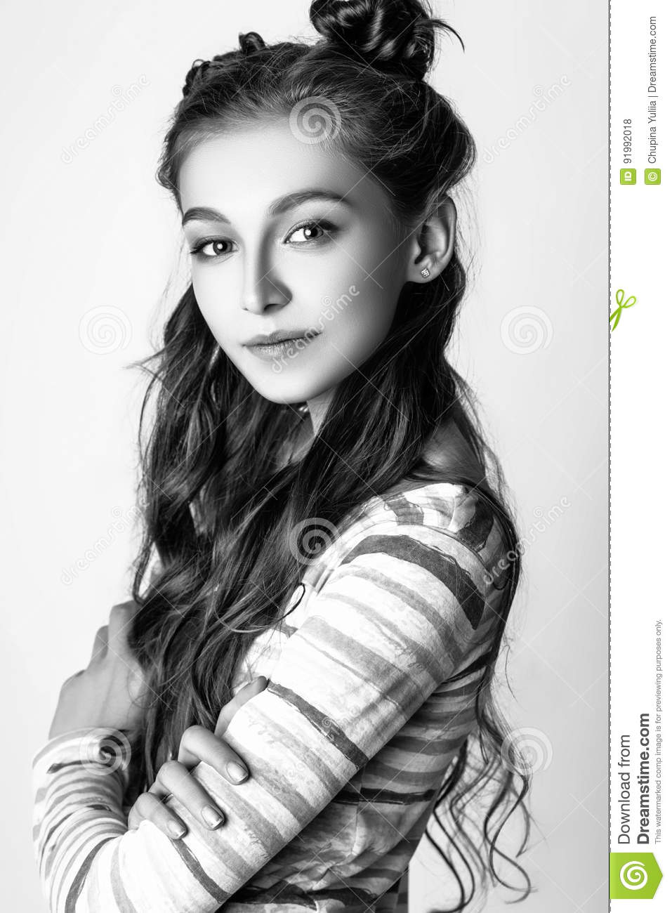 Beautiful teenage girl with long curly hair on a white background studio photo dressed in a blouse in a colorful strip and jeans black and white