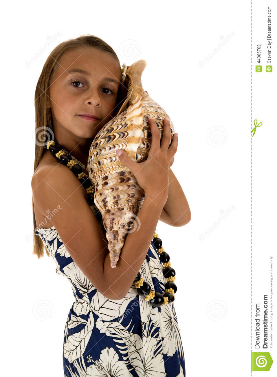 Cute girl wearing a tropical dress and holding a large seashell