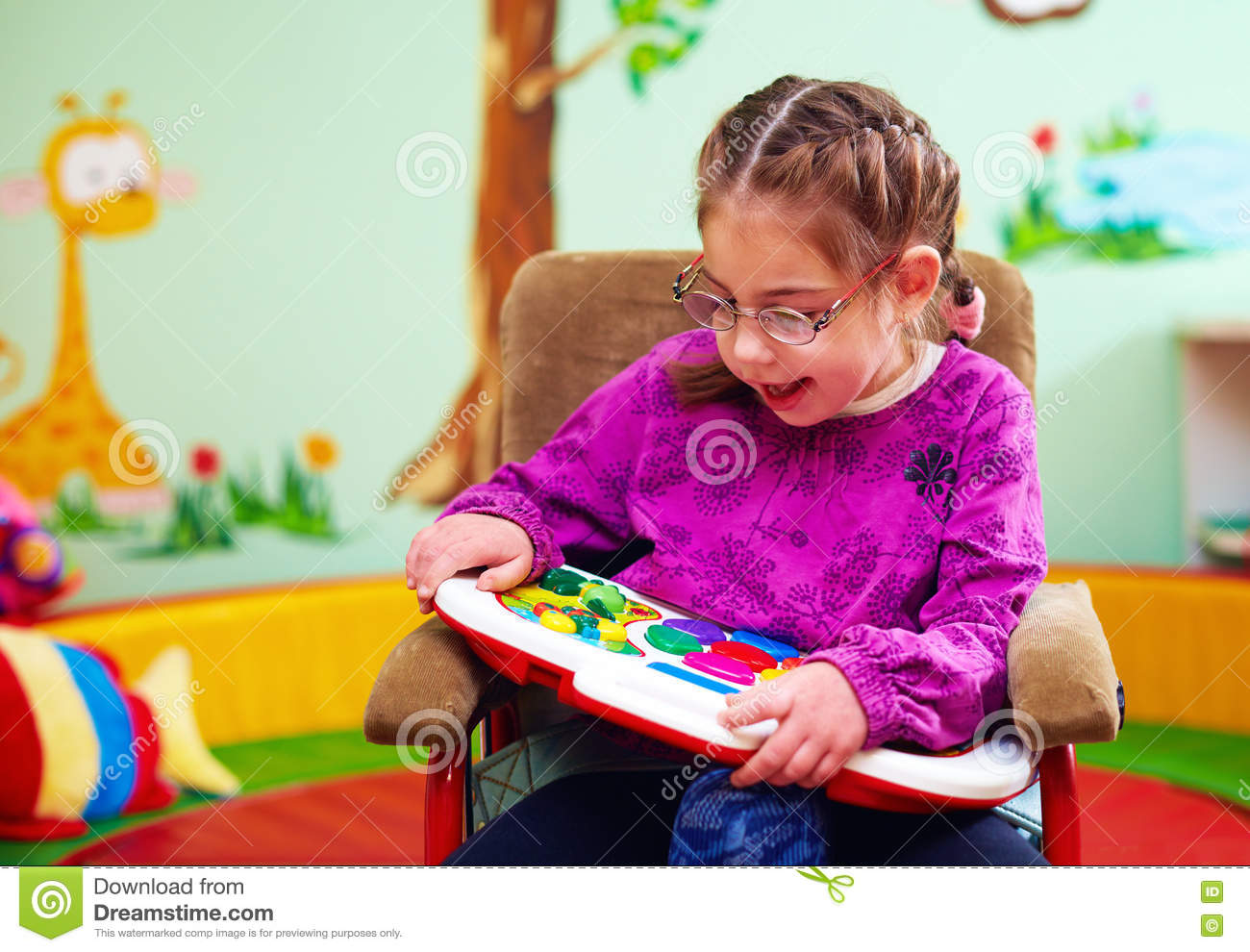 Special Toys For Girls : Cute girl in wheelchair playing with developing toy