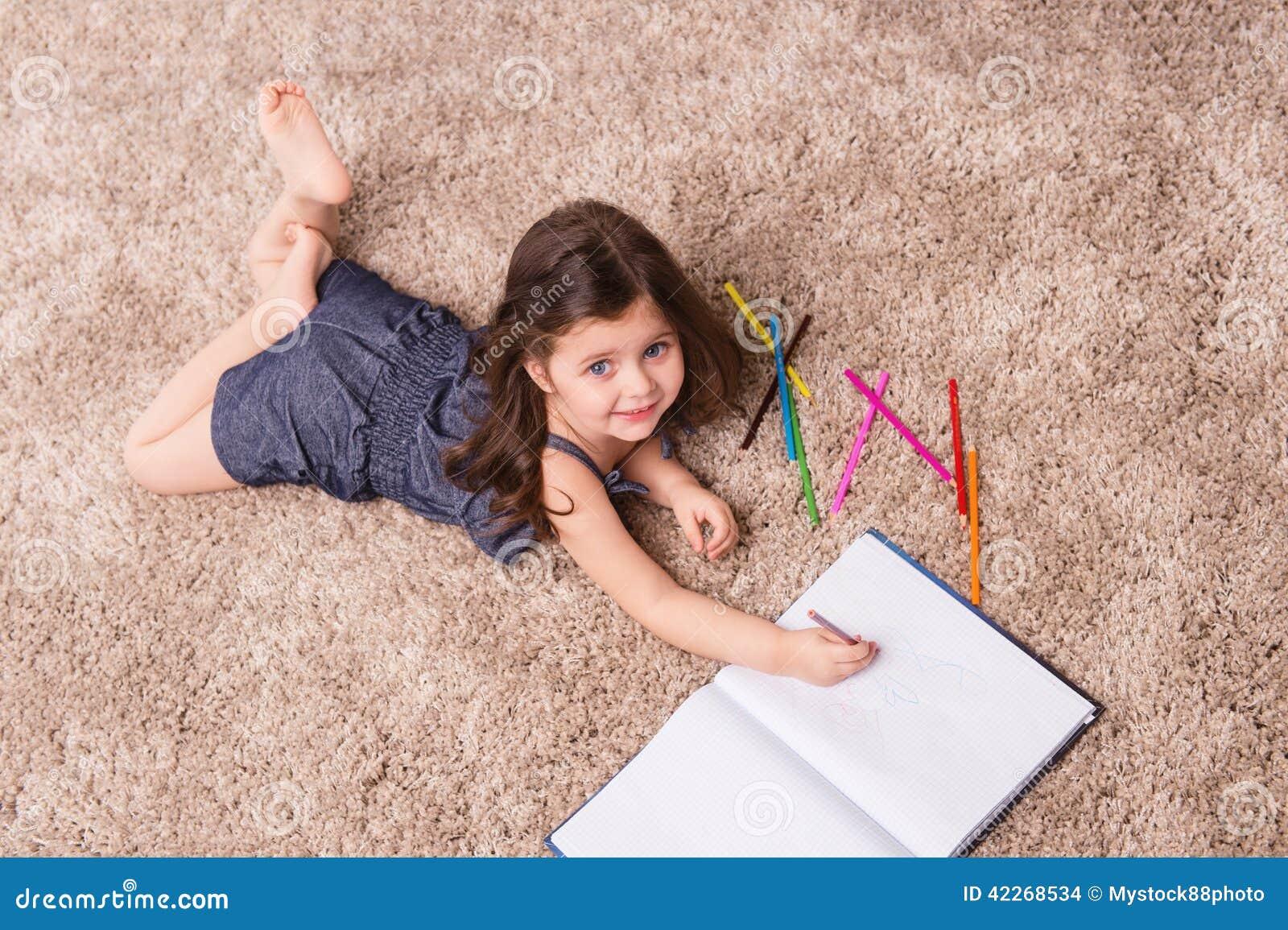 cute girl writing letter on floor  stock photo
