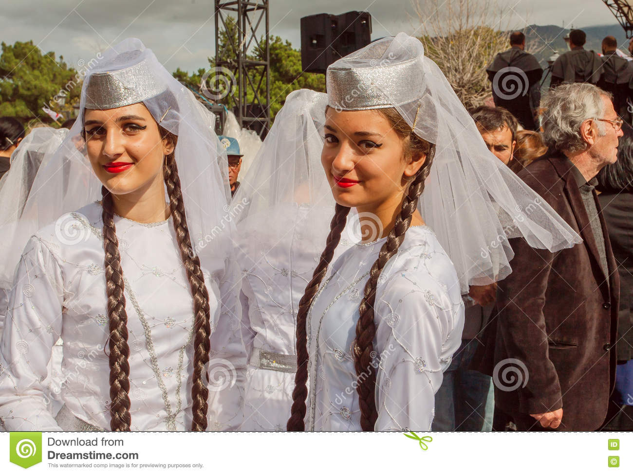 Cute girls in traditional white Georgian costumes ready for dancing performance in Georgia