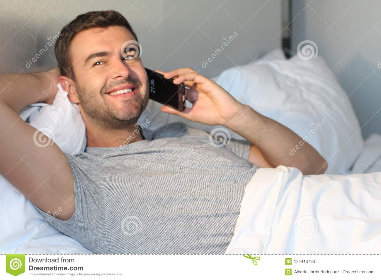 Cute Guy Comfortably Calling In Bed Stock Image - Image of