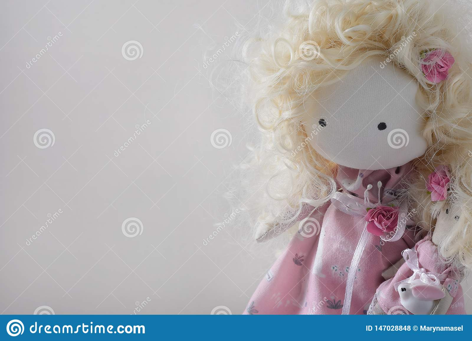 Cute handmade doll with blond curly-hair closeup with copyspace
