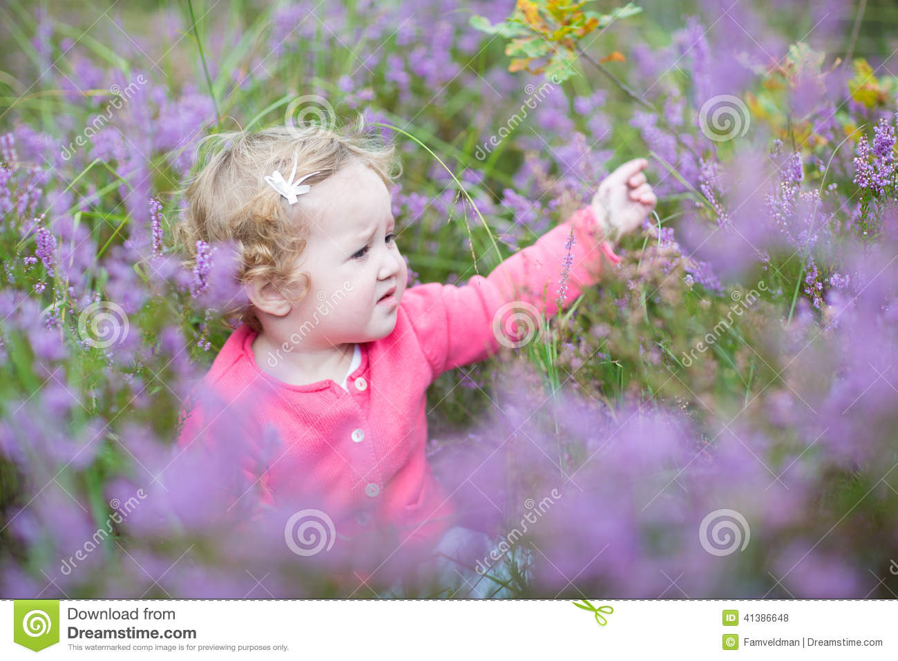 Cute Happy Baby Girl With Beautiful Purple Flowers Stock Photo