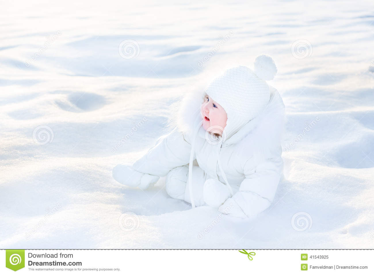 cute happy baby in snow on sunny winter day stock photo