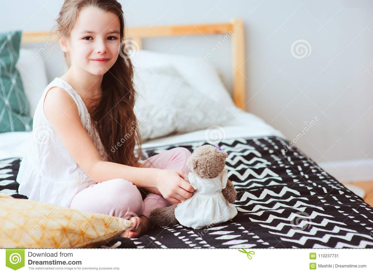 Cute happy child girl relaxing at home on the bed in her room in early morning