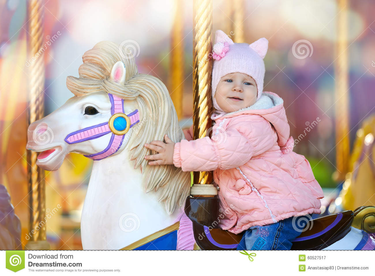Cute happy child riding the horse on the colorful merry go round