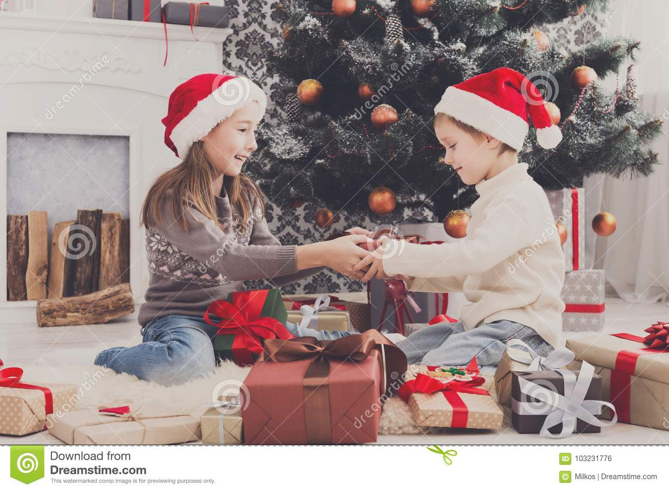 Christmas Presents For Boys.Happy Children In Santa Hats Unwrapping Christmas Presents