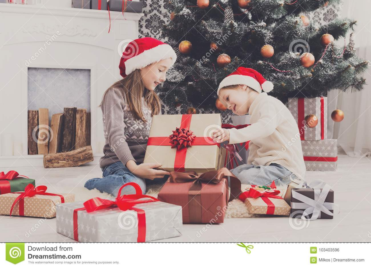 Christmas Presents For Brother.Happy Children In Santa Hats Unwrapping Christmas Presents