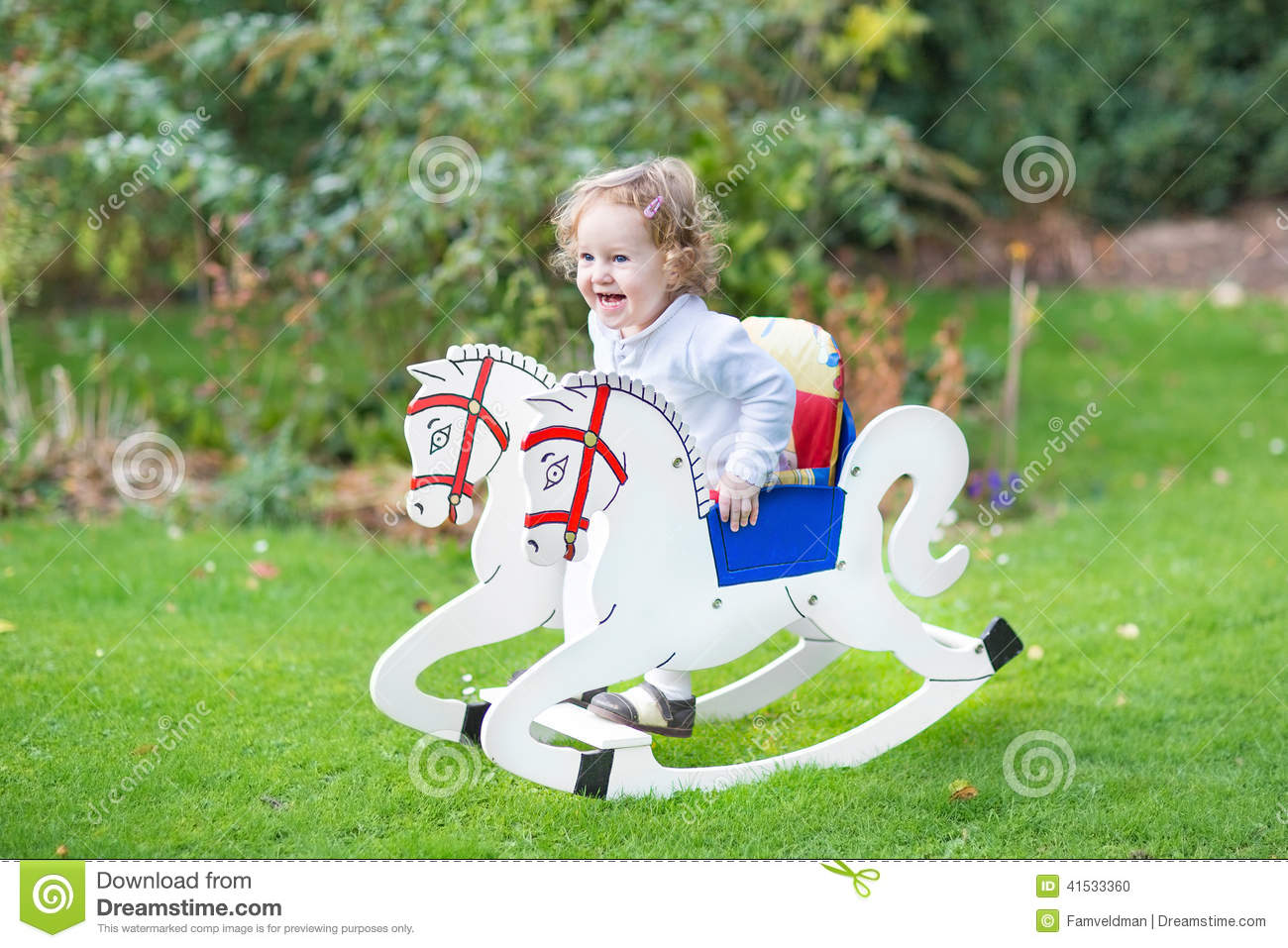 Cute happy girl on rocking horse in the garden