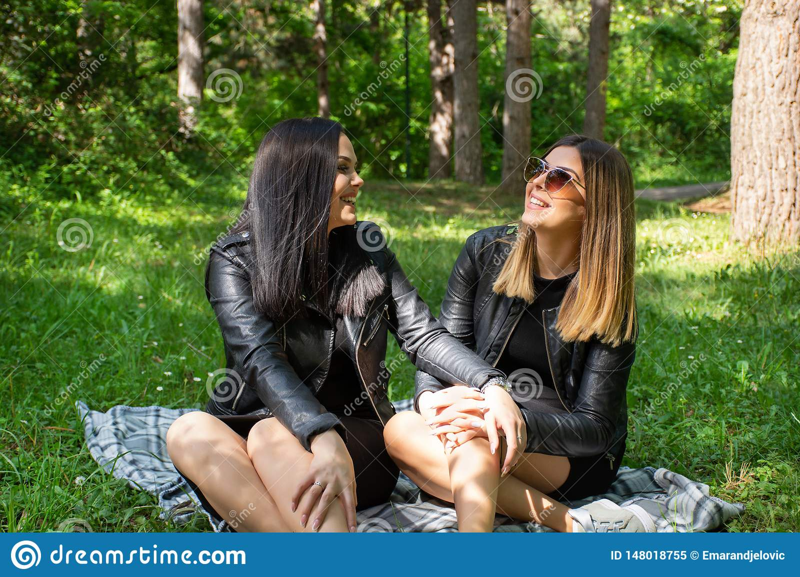 Cute happy girls talking in nature and sitting in the meadow on a blanket, woman laugh and enjoy on a beautiful spring day