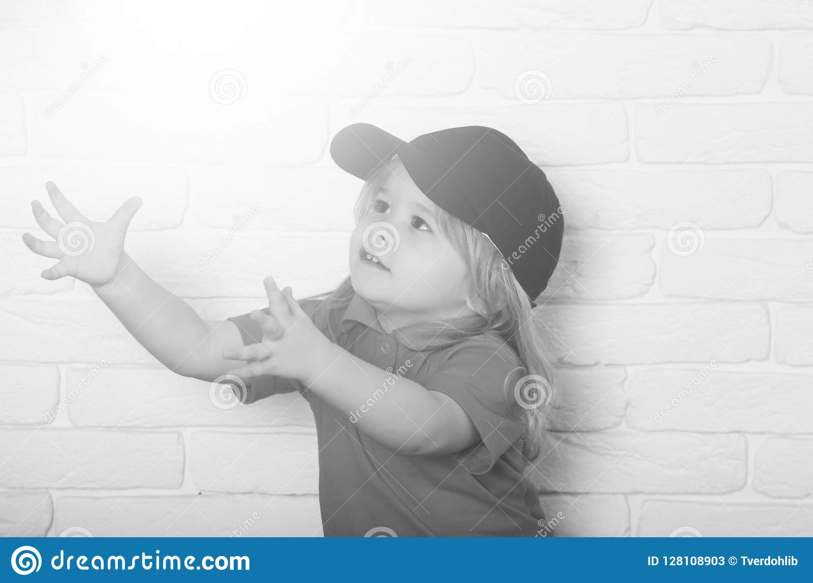 f4b965c610931 Cute happy little boy with long blonde hair in fashionable blue cap and red  shirt with raised hands on white brick wall background