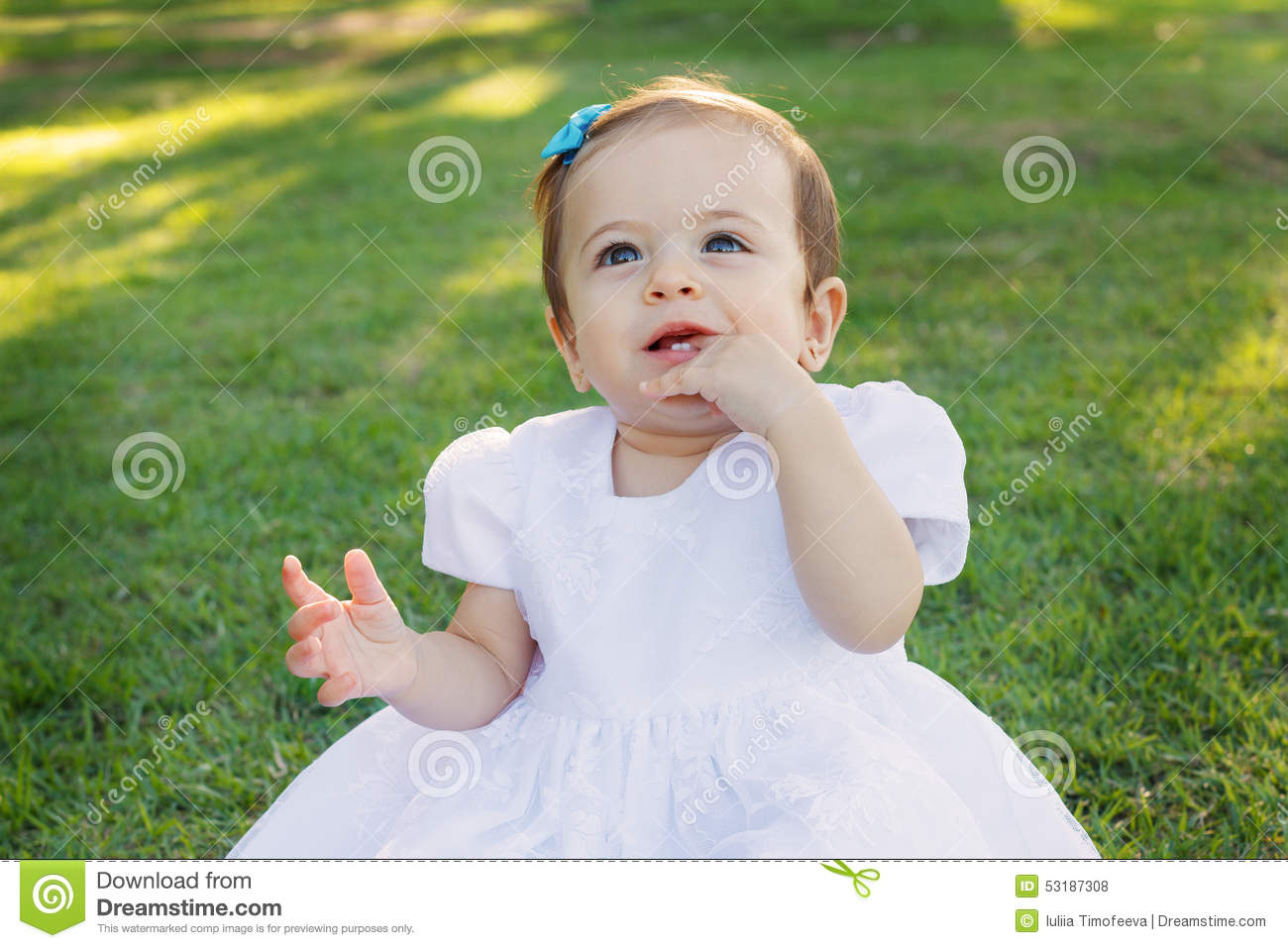cute happy smiling little baby girl in white dress scratching first