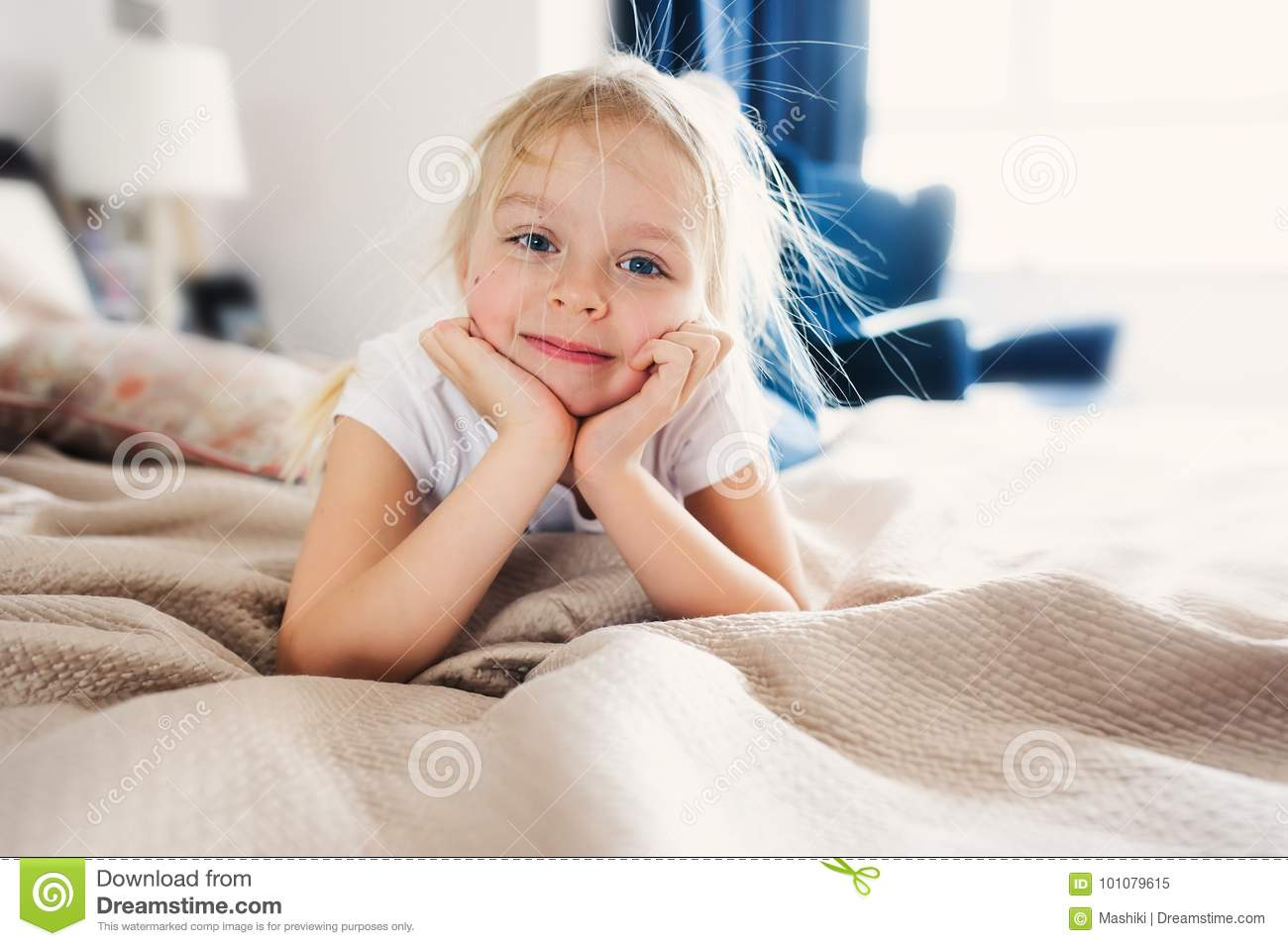 Cute happy toddler girl sitting on bed in pajama. Child playing at home