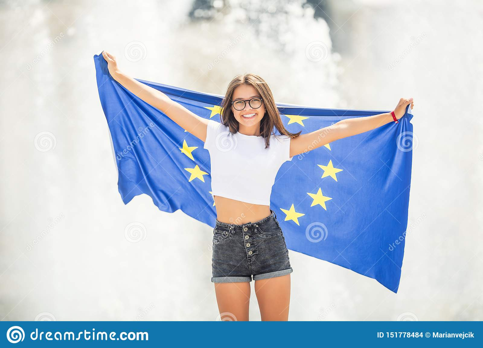 Cute happy young girl with the flag of the European Union in front of a historic building somewhere in europe