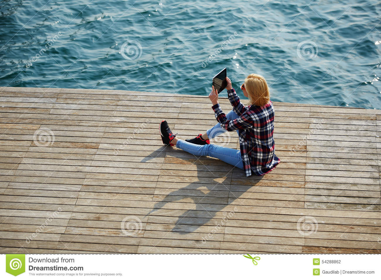 Cute hipster girl relaxing at her sunny holiday photographing outdoors,