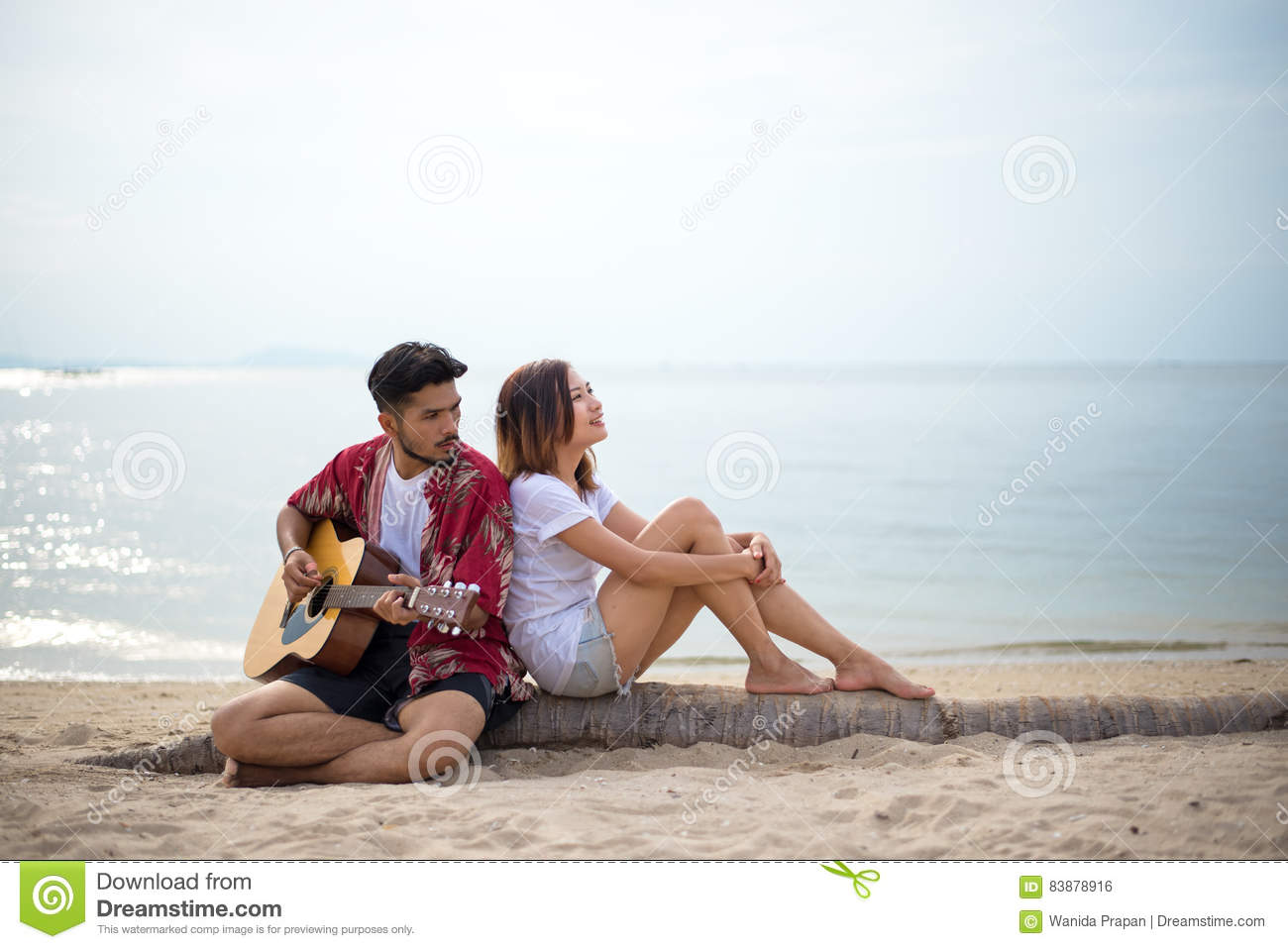 Cute hispanic couple playing guitar serenading