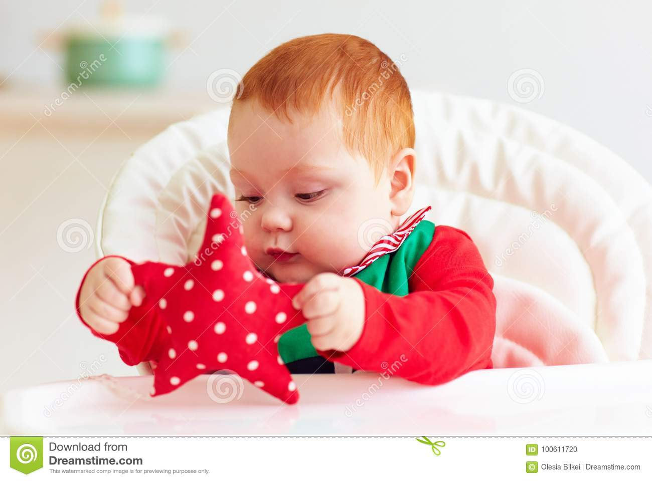 04df808ce47f Cute Infant Redhead Baby Boy In Elf Costume Playing With Red Star In ...