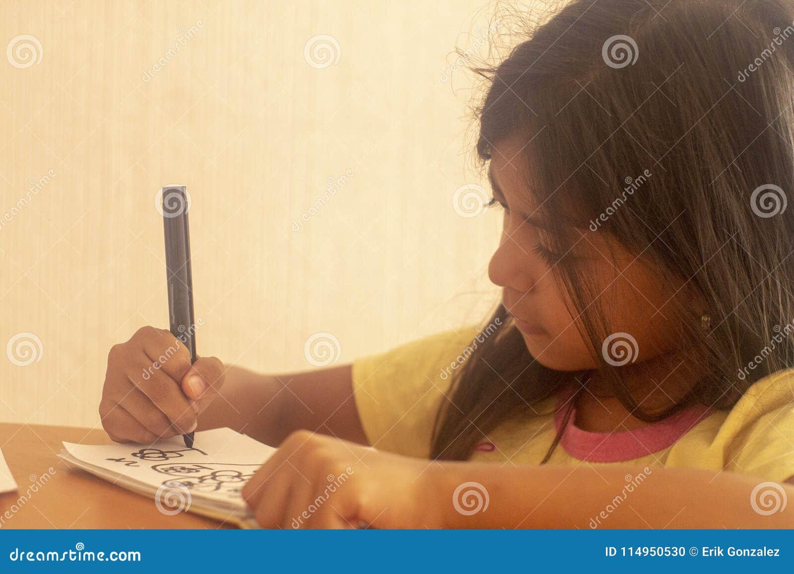 Cute brunette girl doing dubujos on a table