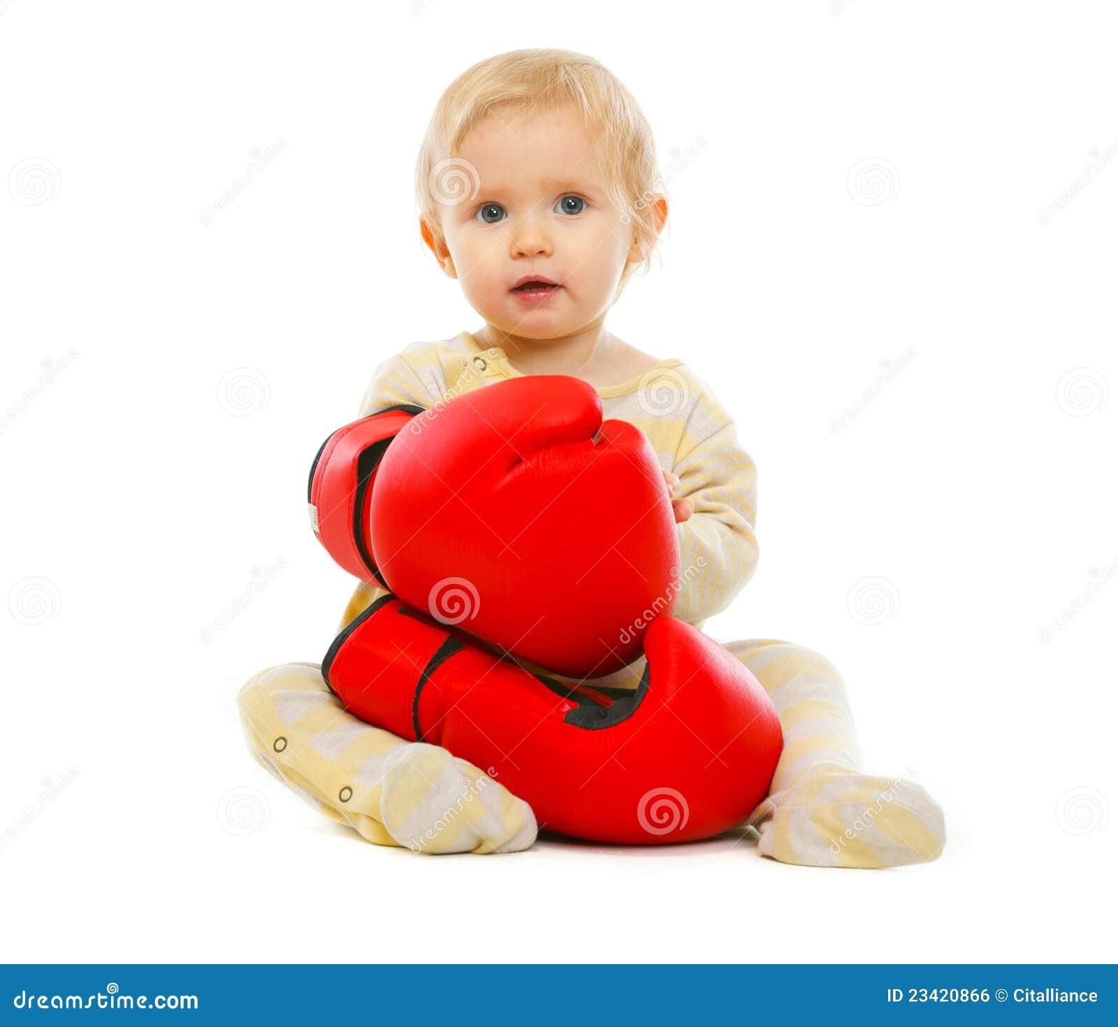 Cute kid in boxing gloves sitting on floor