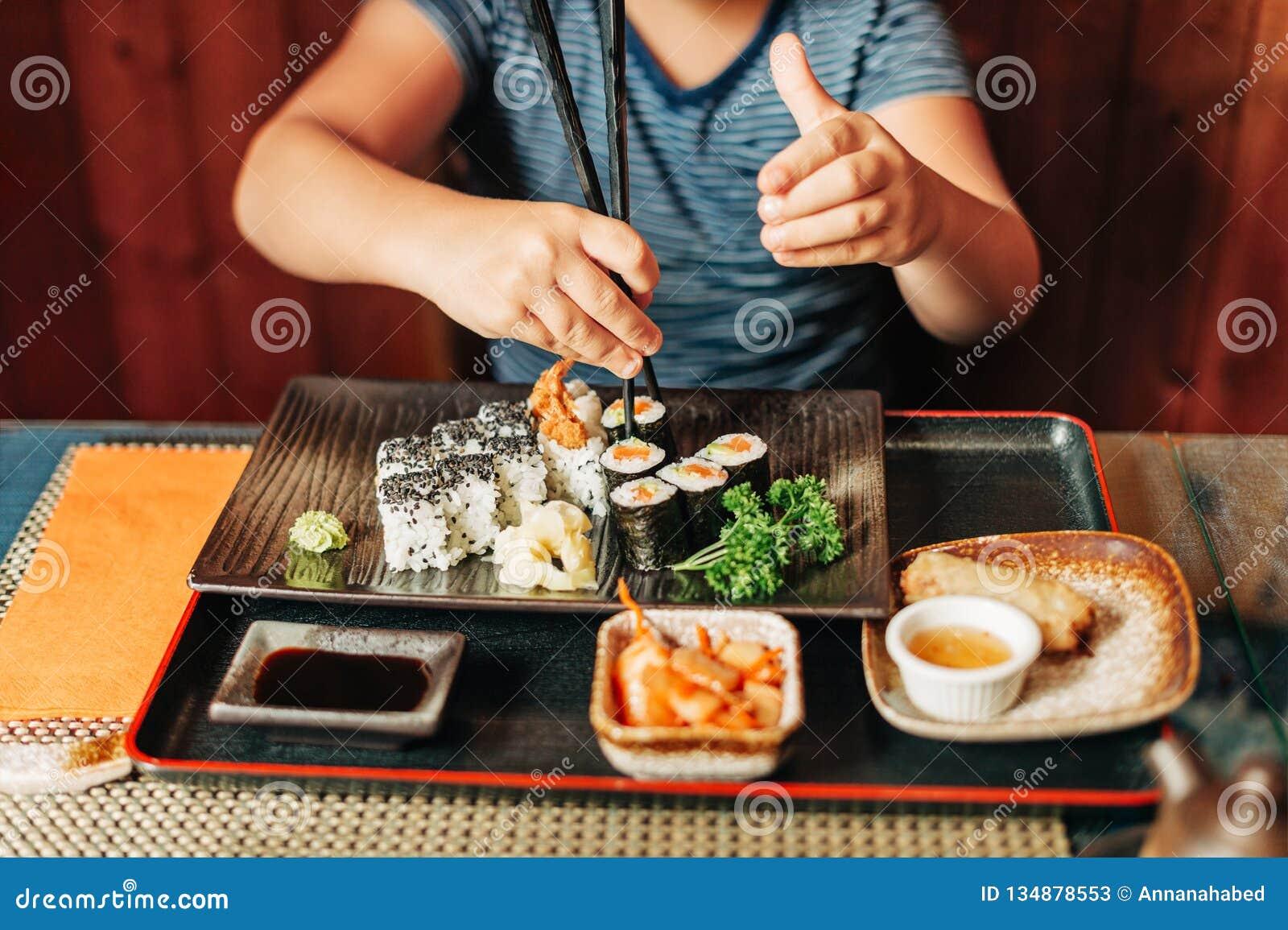 Cute kid boy eating sushi