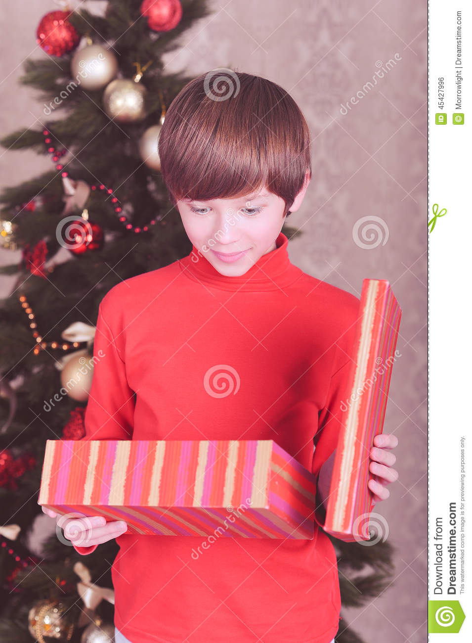 Cute Kid Boy Open Christmas Gift In Room Stock Photo
