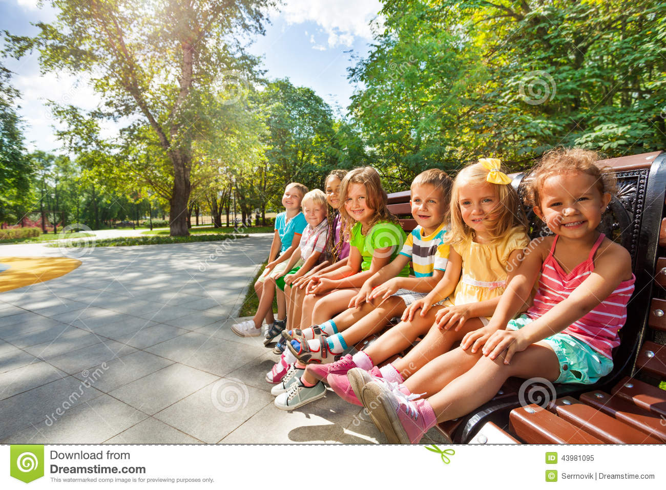 Cute Kids On The Bench In Park Toggether Stock Photo
