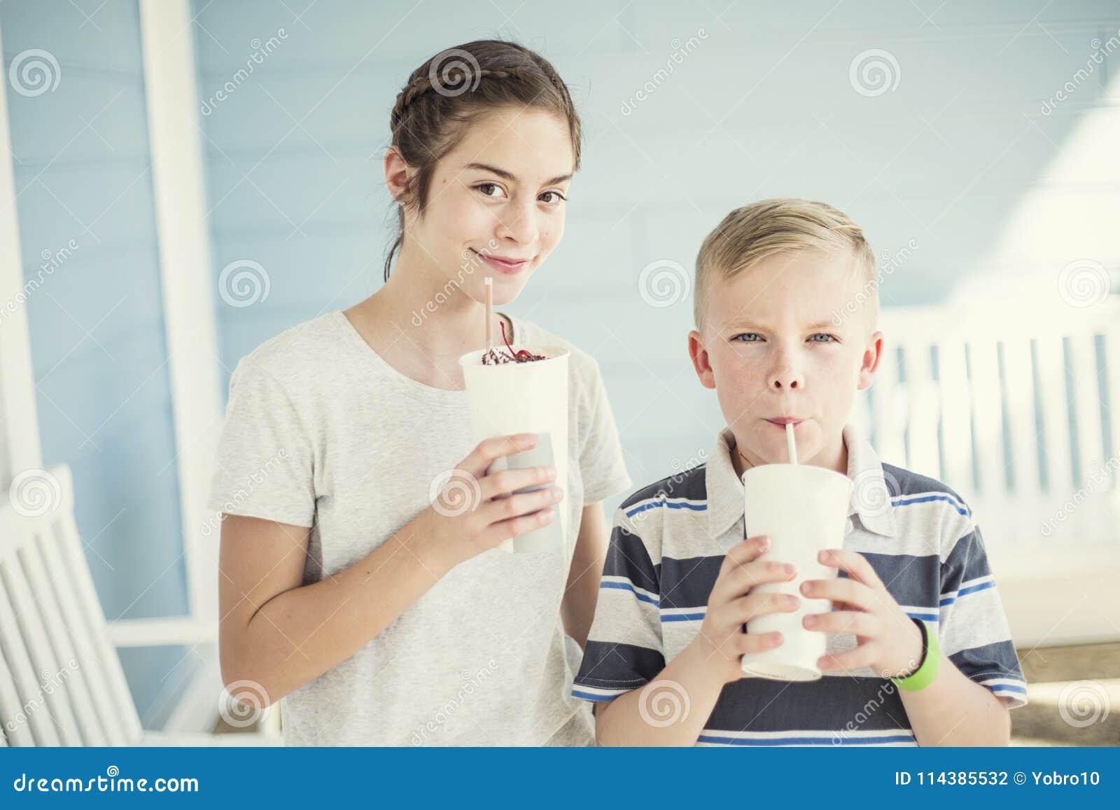 Cute kids drinking milkshakes or flavored drinks together