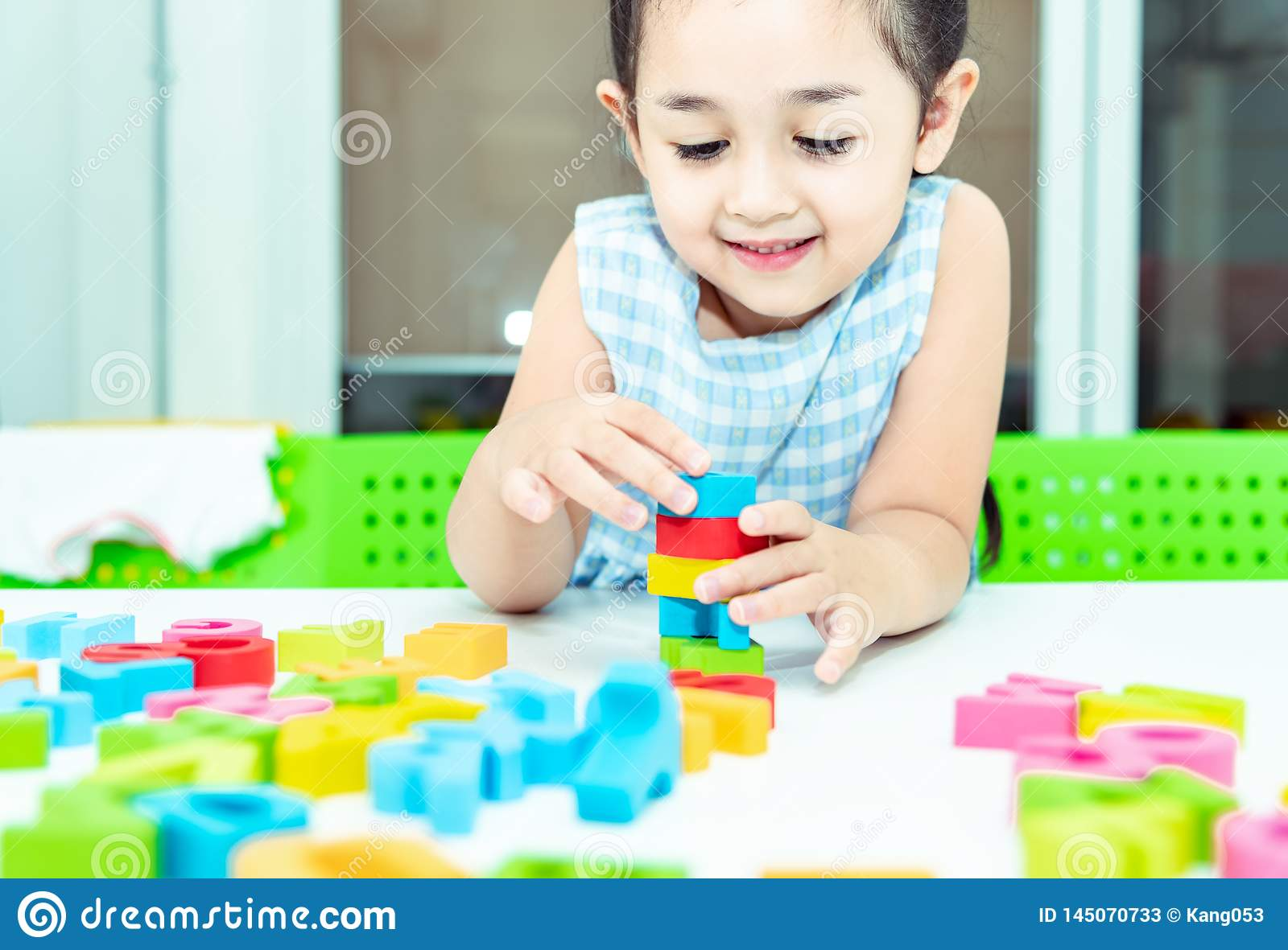 Cute kids female playing with toy designer on the floor at home. Child girl exciting while playing with alphabet colorful blocks.