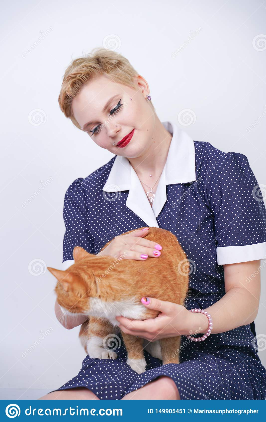 Cute kind woman with short hair in pinup polka dot dress holding her beloved pet on a white background in the Studio. plus size ad