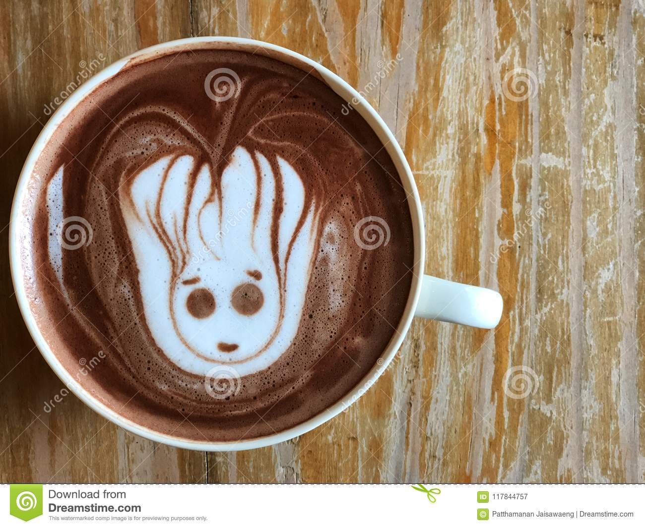 Cute Latte art coffee on the wooden table, latte art coffee shape look like `Groot`