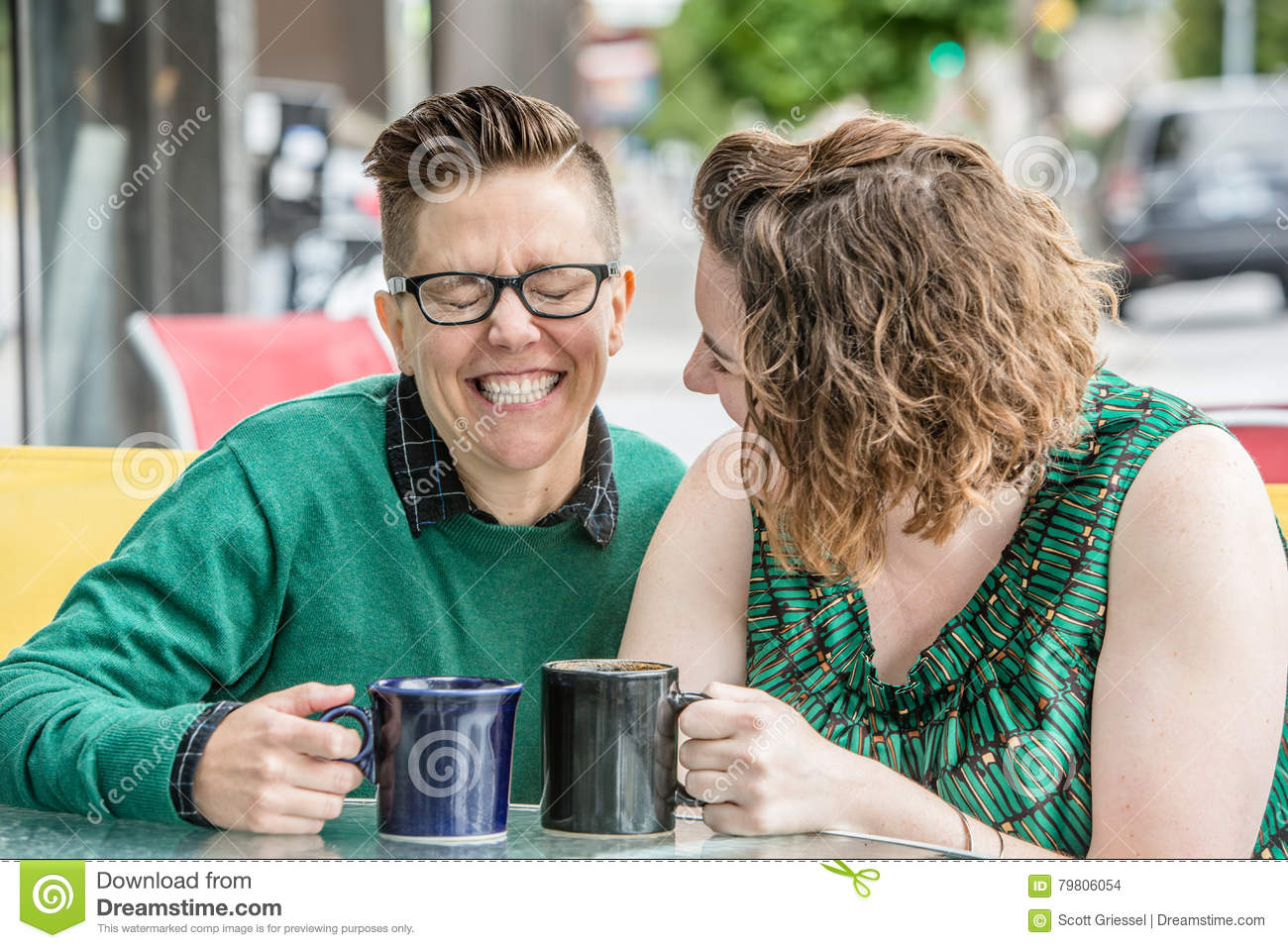 Cute lesbian couple joking outside at bistro