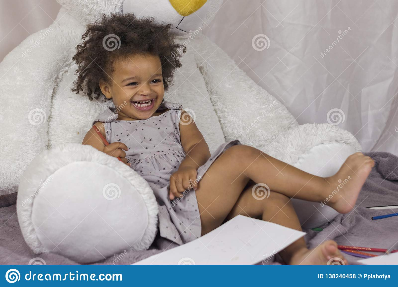 ae15f9154e4 Cute little african american girl laying on big white teddy bear and  laughing