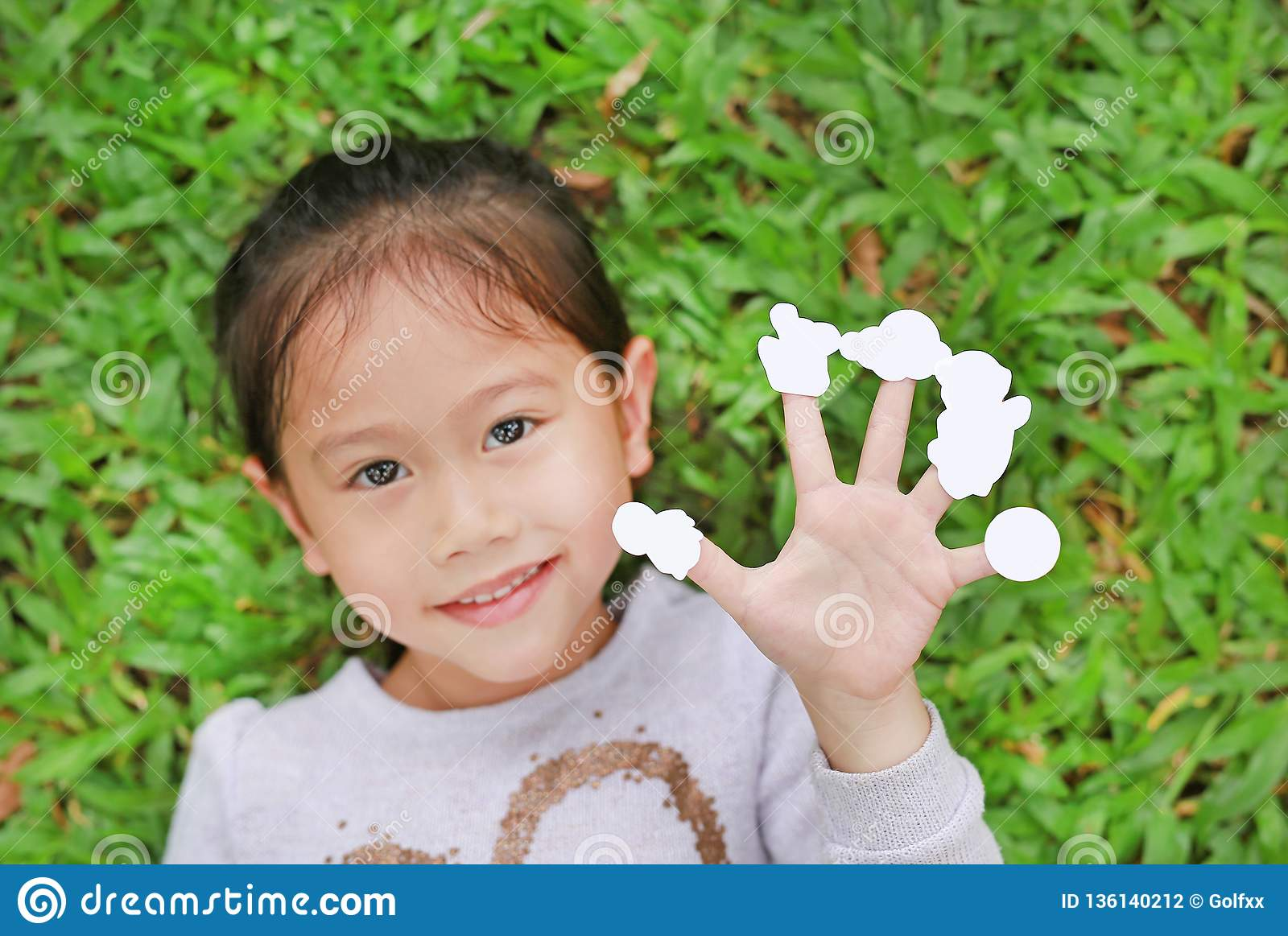 Cute little Asian kid girl lying on green grass lawn with showing empty white stickers on her fingers. Focus on hand