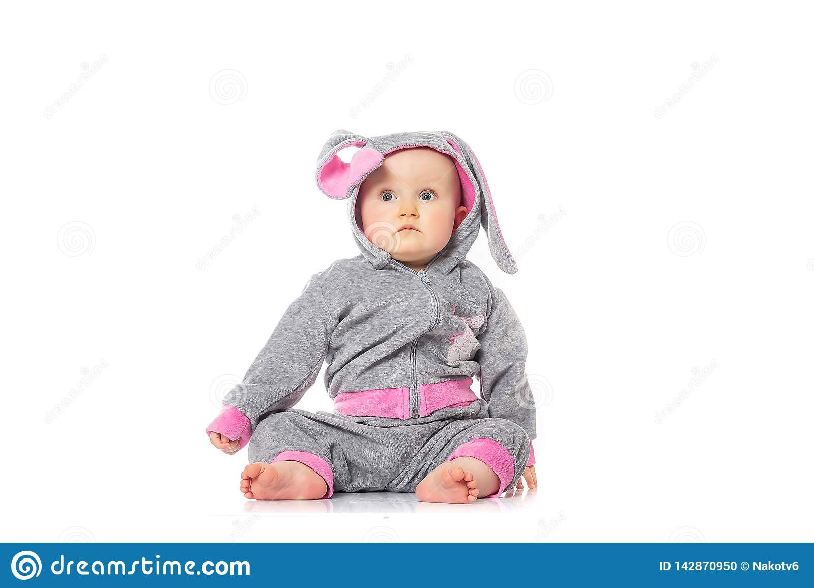 Cute little baby in bunny costume sitting on white background. children`s games. baby emotions