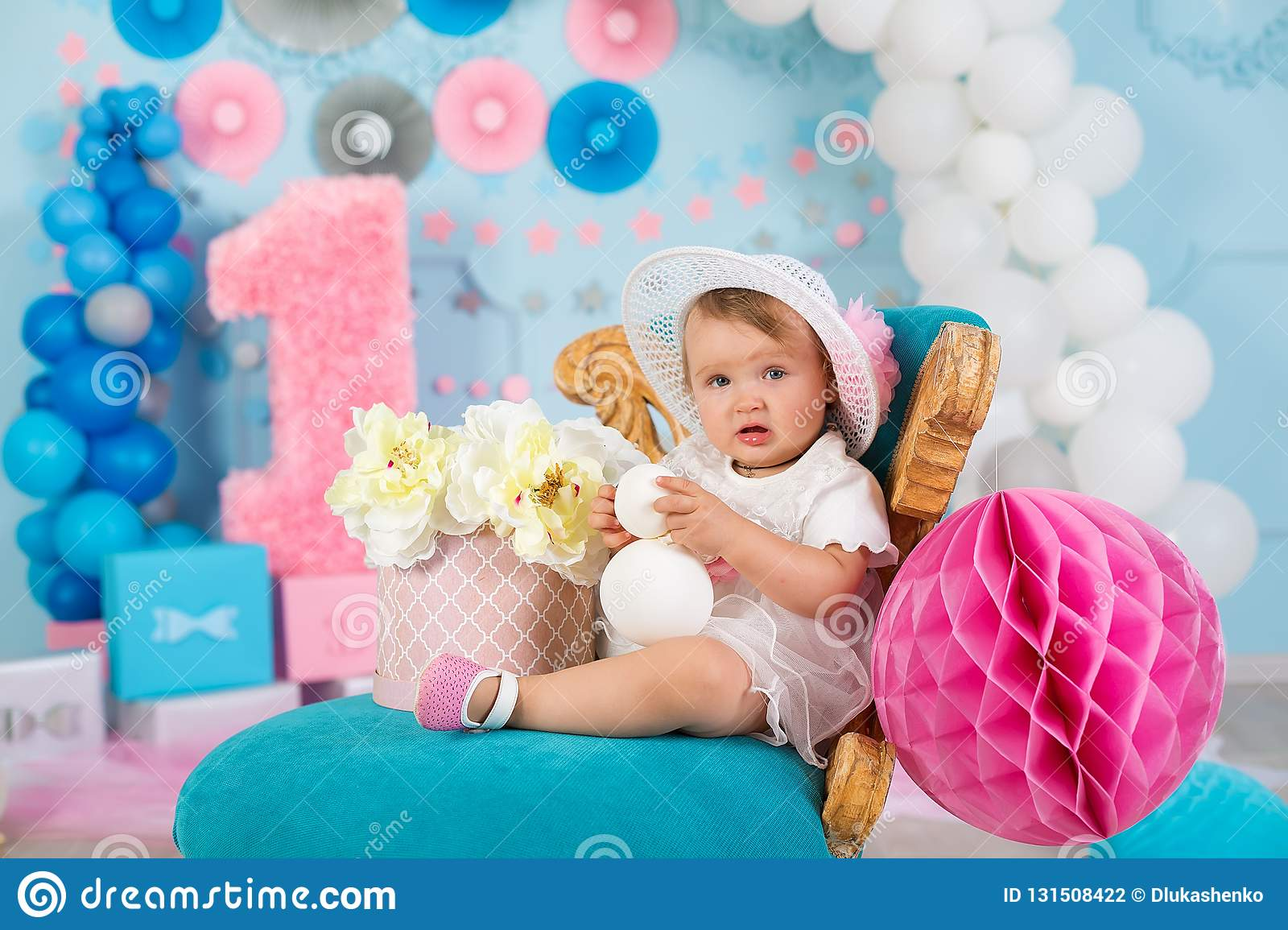 Cute little baby girl with big blue eyes wearing tutu hat and flower in her hair posing sitting in studio decorations with number