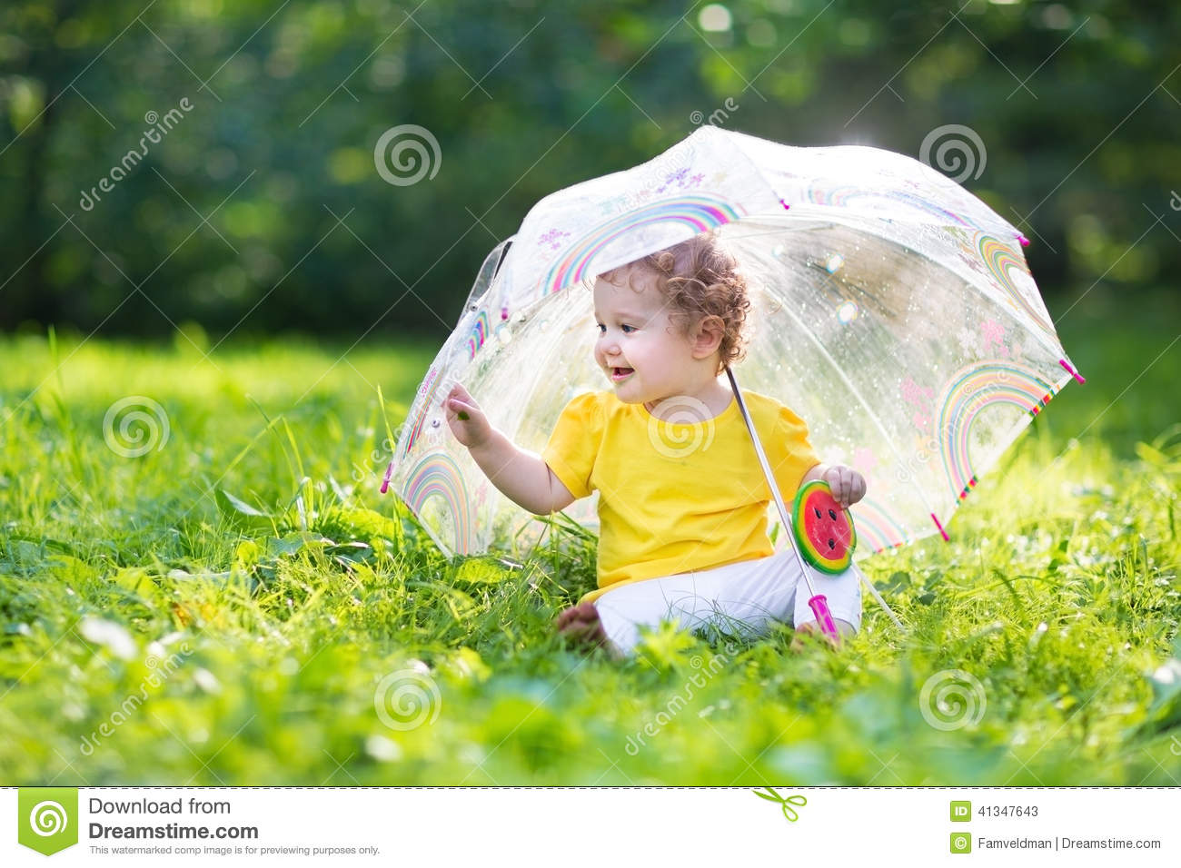 cute little baby girl in the garden under an umbrella stock image