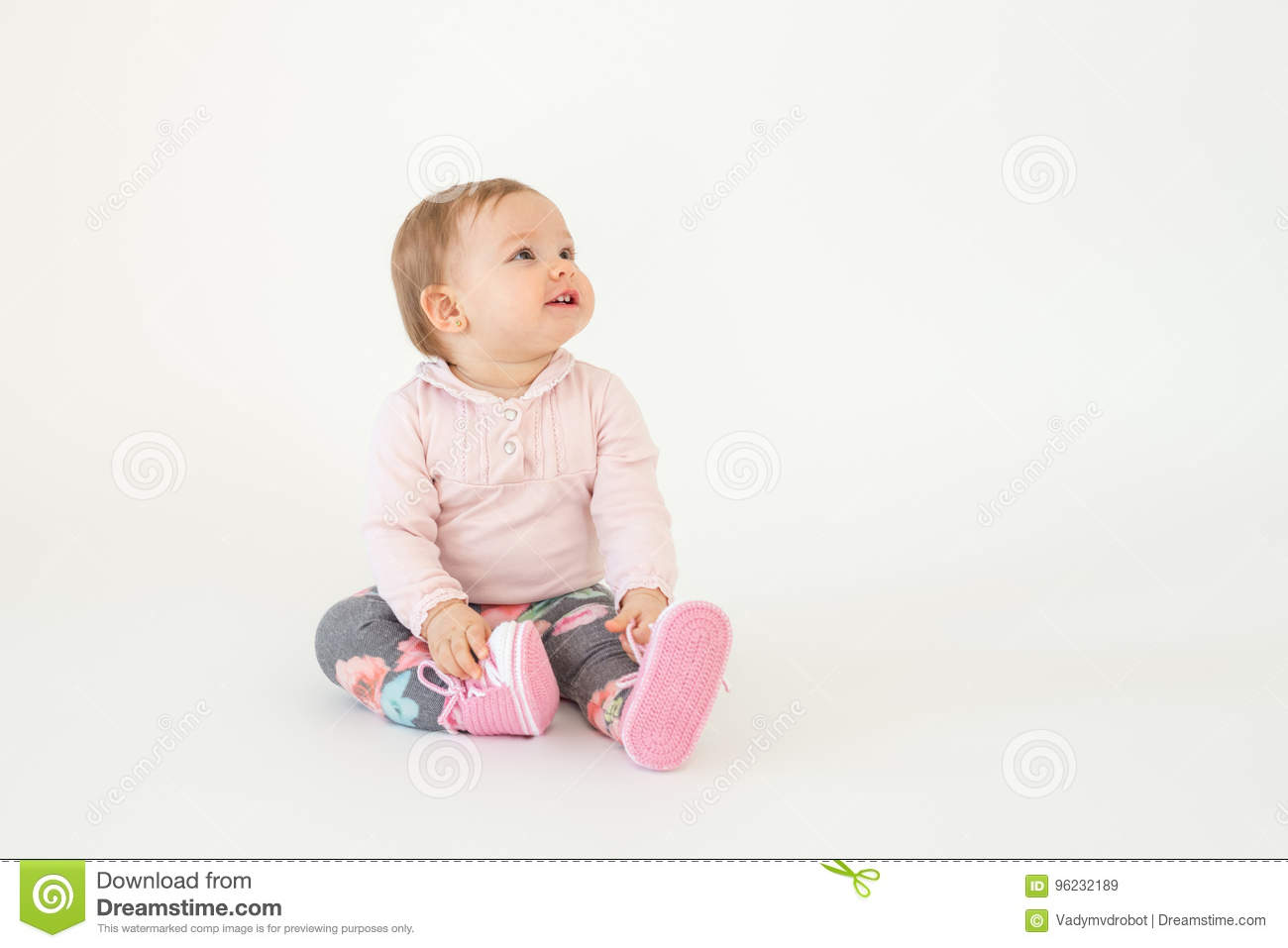 93d964d6b75c Photo of cute little baby girl sitting on floor isolated over white  background. Looking aside.