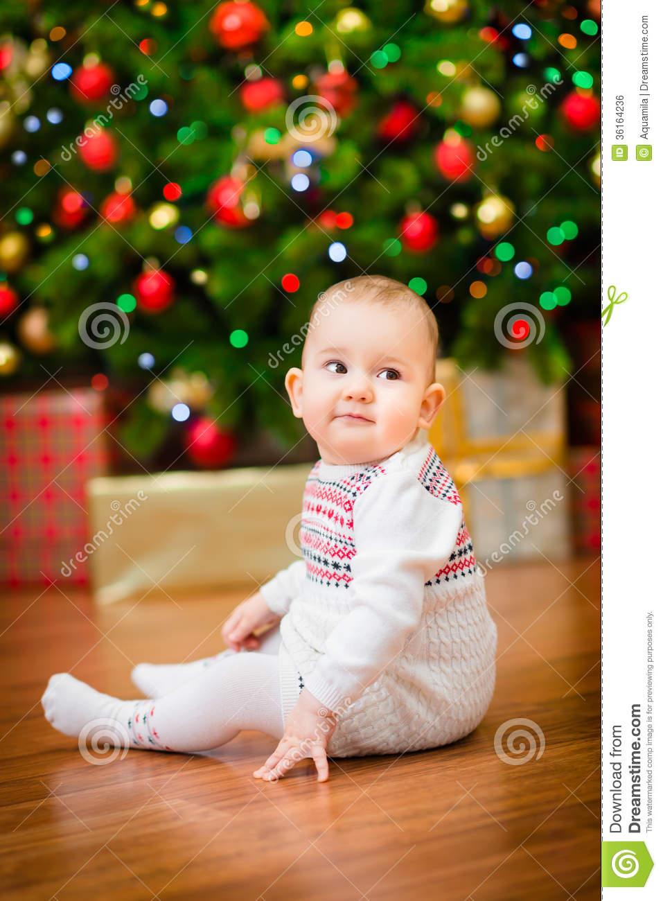 Cute Little Baby Girl Sitting In Front Of Christmas Tree