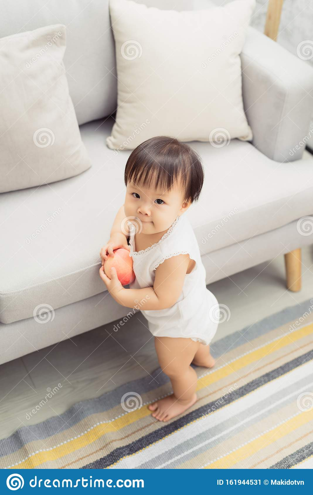 Cute Little Baby Girl Standing Next To Sofa At Living Room Stock