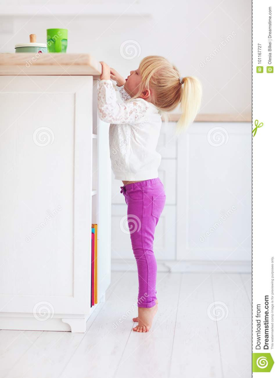 Cute Little Baby Girl Trying To Reach A Bottle From Kitchen Desk ...