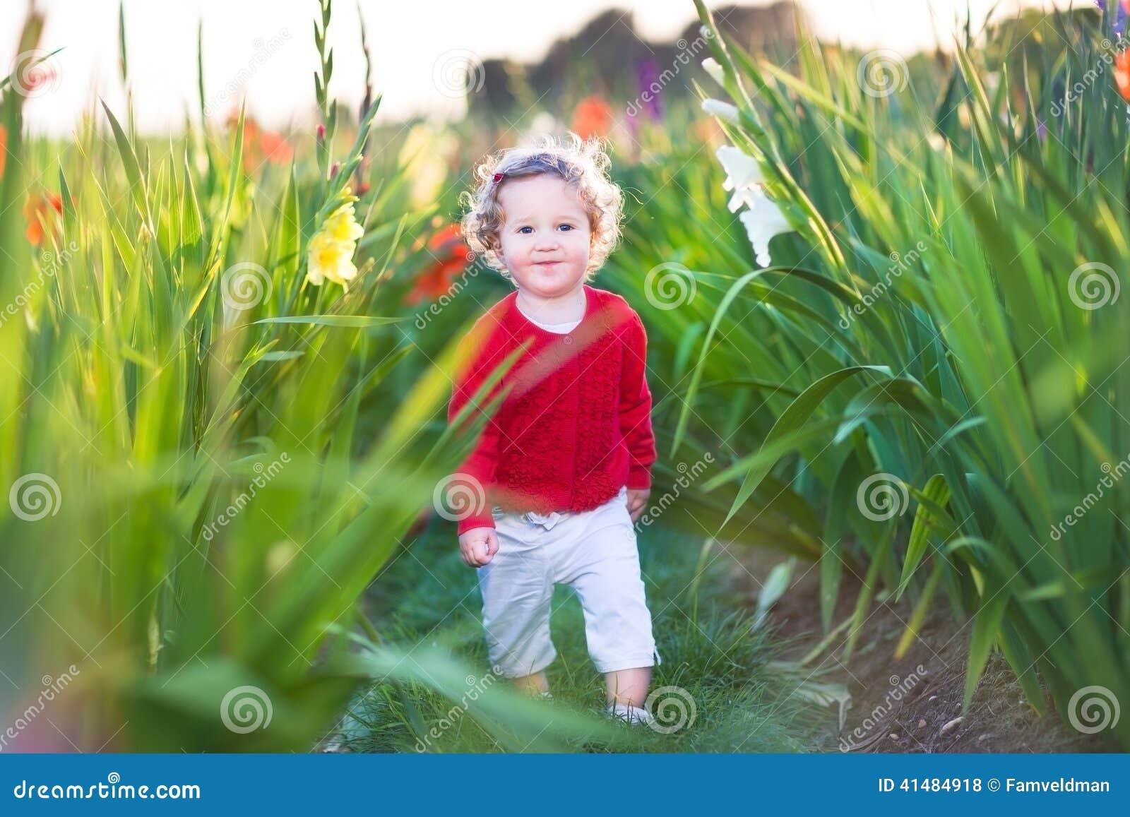Cute Little Baby Girl Walking In A Field On Flowers Stock Photo