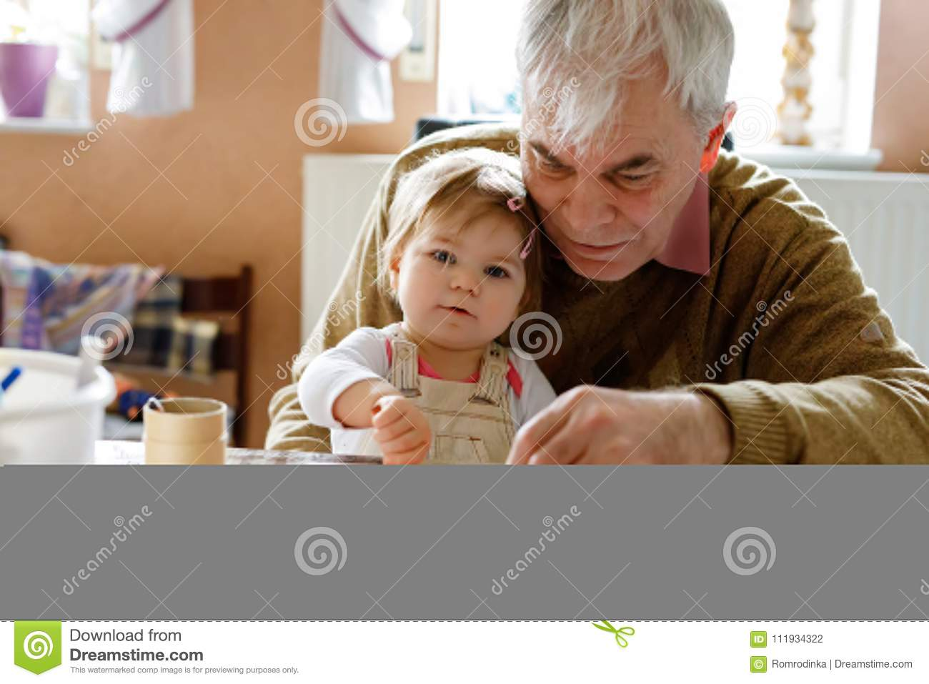 Cute little baby toddler girl and handsome senior grandfather painting with colorful pencils at home. Grandchild and man