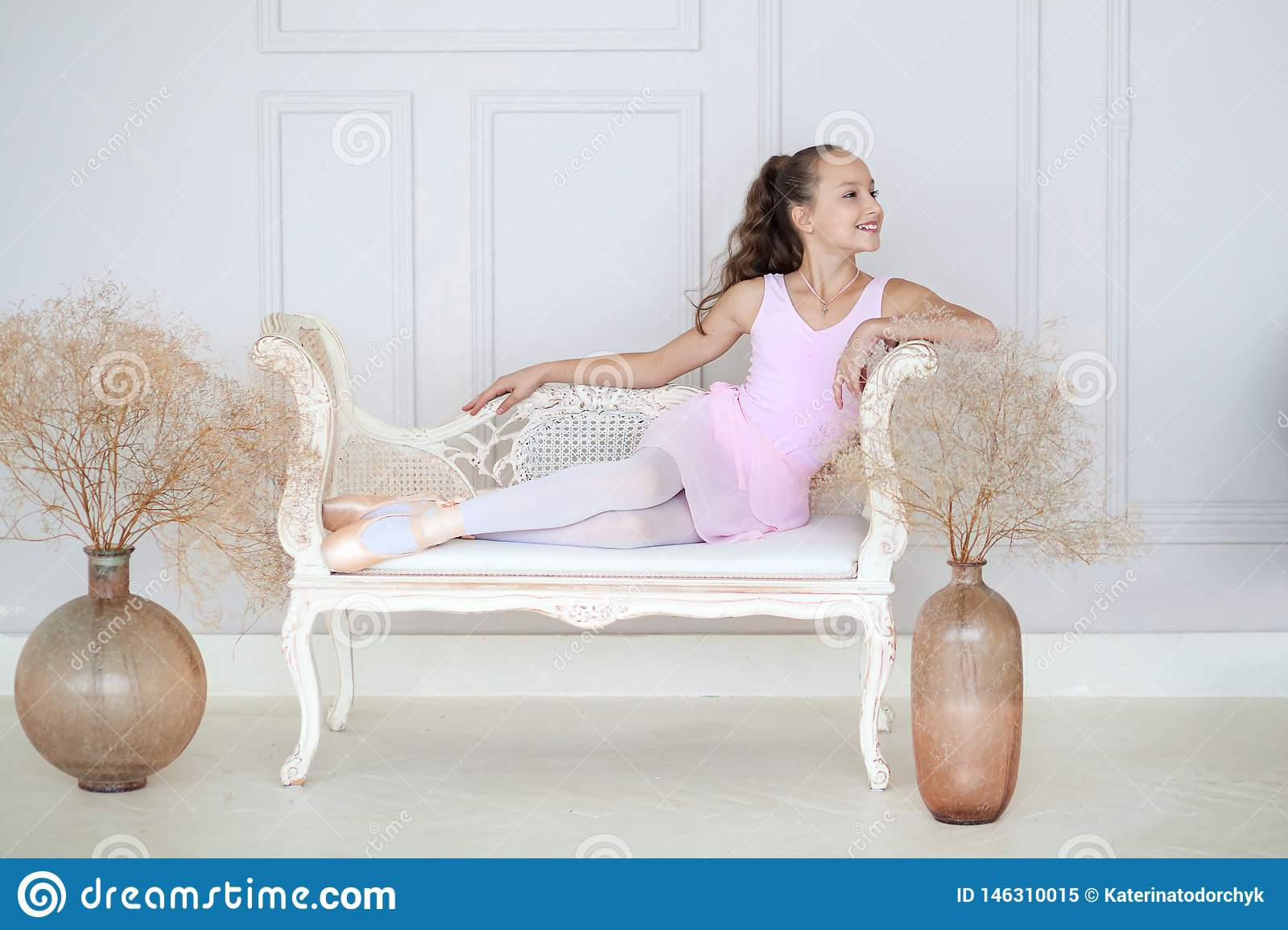 A cute little ballerina in a pink ballet costume and pointe sits on the sofa. Ballerina in the dance class. The girl is studying b