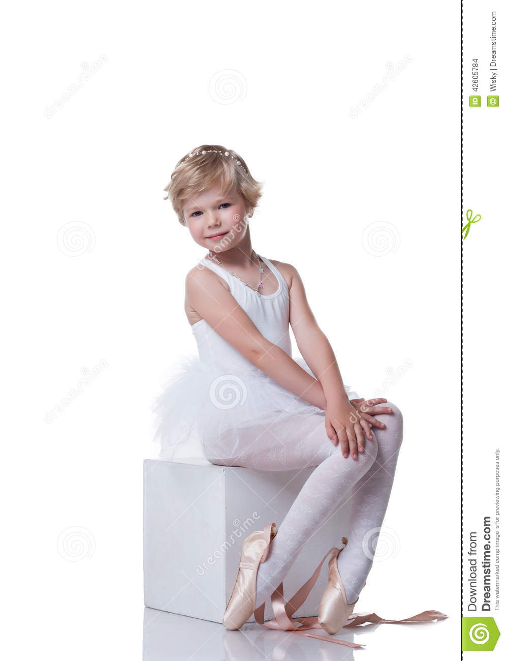 Cute little ballerina sitting on cube in studio