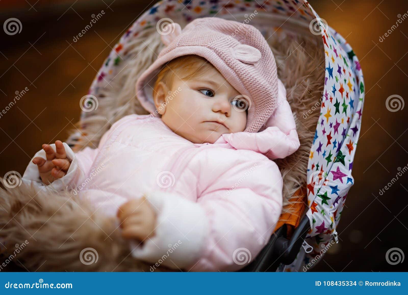 1786fe38b6d8 Cute Little Beautiful Baby Girl Sitting In The Pram Or Stroller On ...