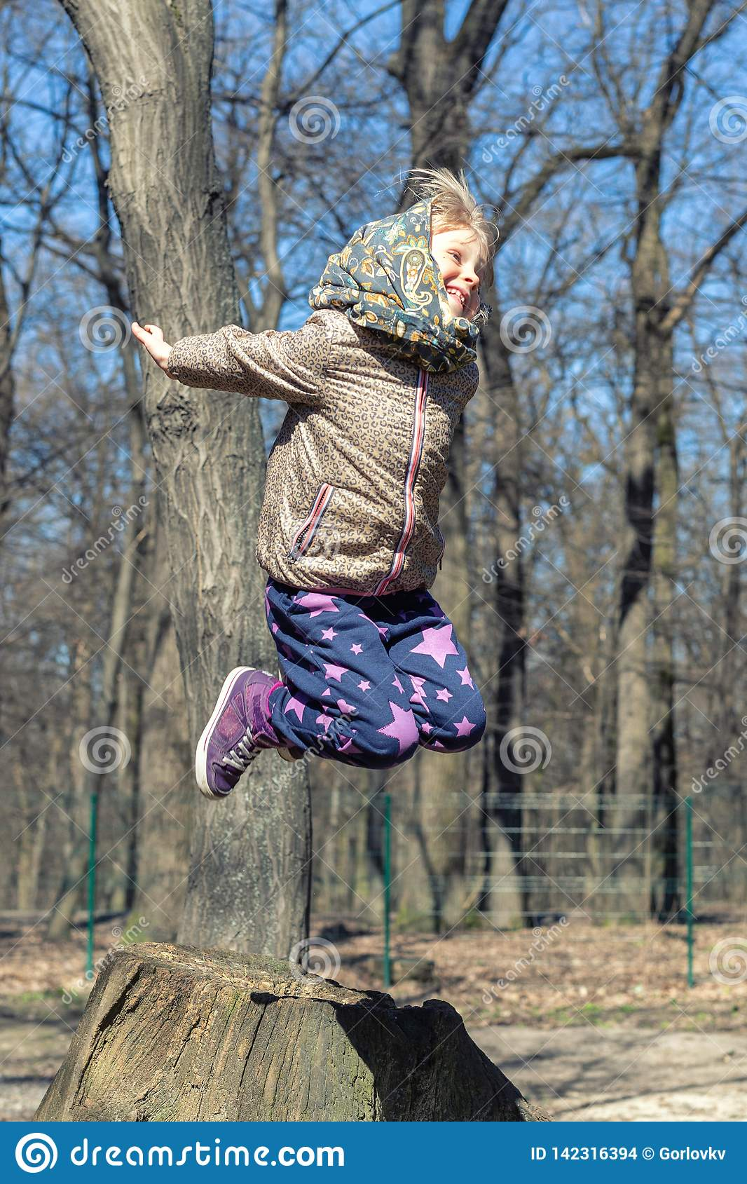 Cute little blond kid girl having fun outdoors. Child in casual sport wear and kerchief jumping high from tree stump in forest