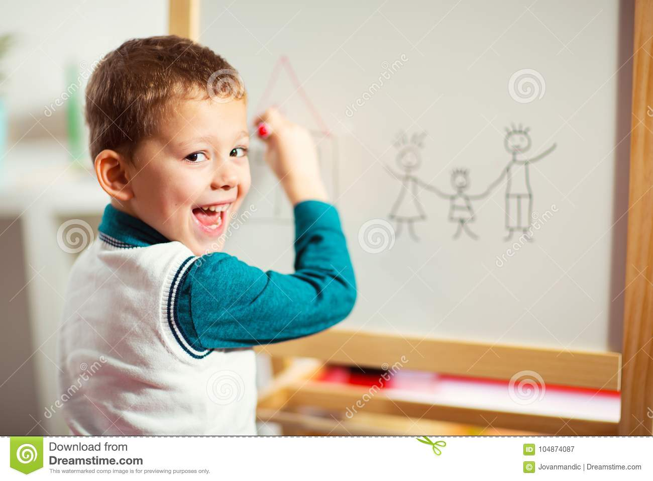 Cute little boy drawing on white board with felt pen and smiling