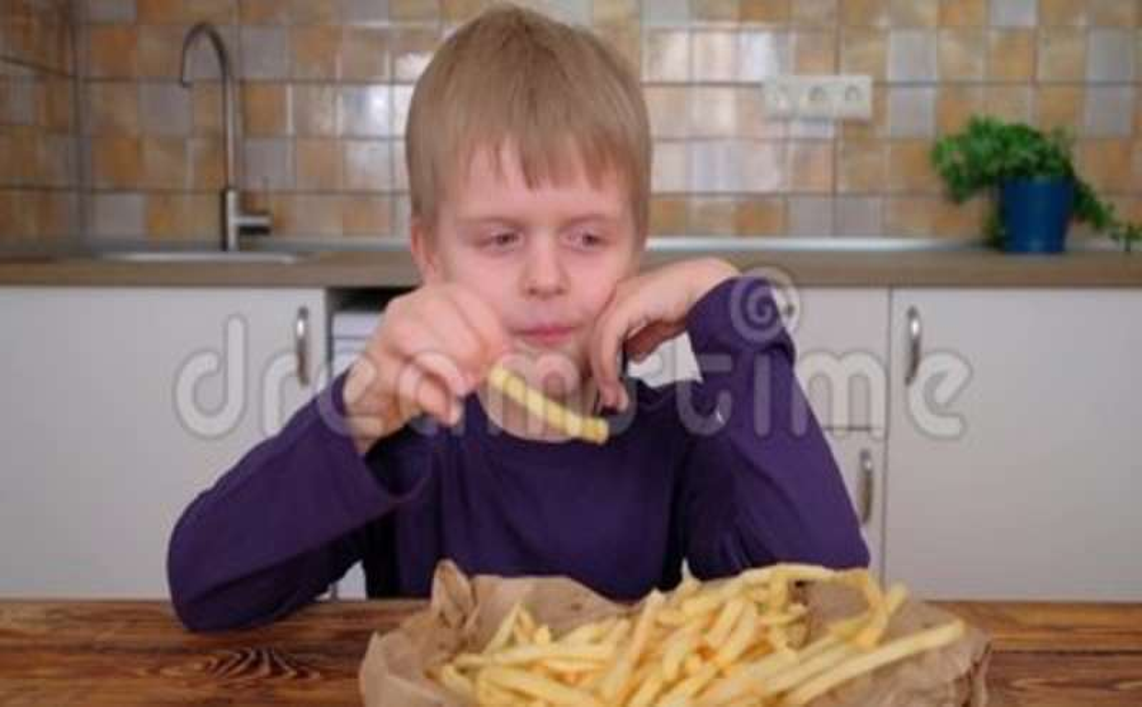 c6f11180b9cf0 Cute Little Boy Enjoying French Fries In Kitchen Stock Video - Video ...